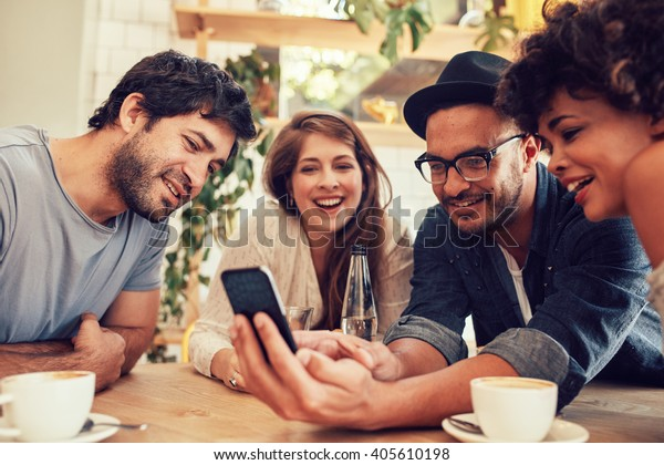 Group of young people sitting in a cafe and looking at the photos on smart phone. Young men and women meeting at cafe table and using cell phone