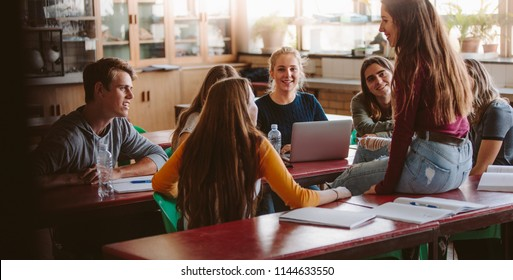 Group of young people sitting in the classroom and talking. University lecture room with students chatting during break.