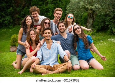 Group of young people sitting in the grass, they pose for the photo smiling