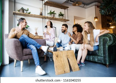 Group of young people sitting at a modern cafe interior, talking and enjoying time together, drinking coffee and having fun