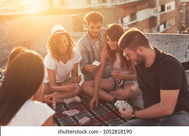 Group of young people sitting on a picnic blanket, having fun while playing cards on the building rooftop. Focus on the guy on the right