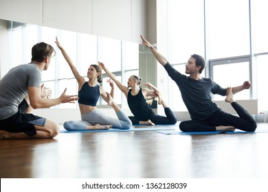Group of young people sitting on exercise mats and raising hands up while doing one-legged king pigeon pose, yoga coach giving advice to them