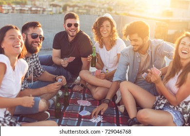 Group of young people sitting on a picnic blanket, having fun while playing cards on the rooftop. Focus on the couple in the middle