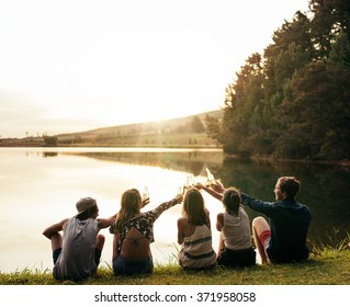 Group of young people sitting in a row at a lake. Young friends toasting and celebrating with beers at the lake.