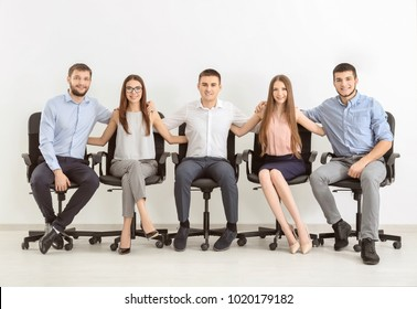 Group of young people sitting together on chairs against white wall. Unity concept
