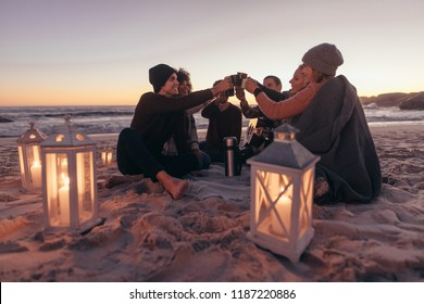 Group of young people sitting together at the beach toasting coffee on warm evening. Friends partying at the beach with coffee.