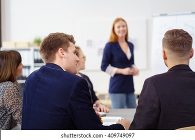Group of young people in small office staff meeting from back of man in jacket looking at co-workers discussing something