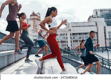 Group of young people in sports clothing jogging while exercising on the stairs outdoors