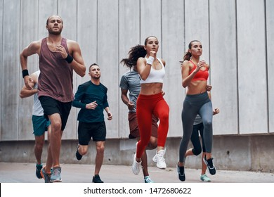 Group of young people in sports clothing jogging while exercising outdoors