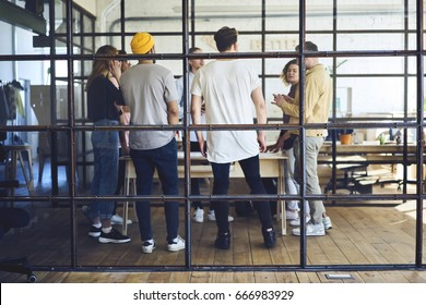 Group of young people standing around table in contemporary office and talking. Group of stylish creative colleagues brainstorming at meeting.