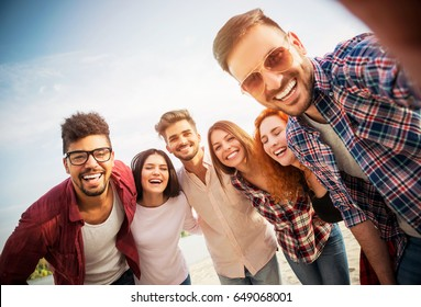 Group of young people standing in a circle, outdoors, making a selfie