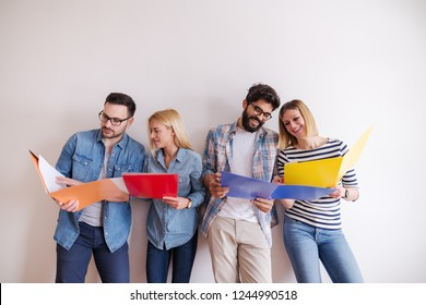 Group of young people standing and looking at folders they holding in hands while standing against the white wall. Start up business concept.