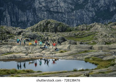 Group of young people is standing next to the small lake and having fun. Beautiful reflections in the water. Preikestolen, Norway.
