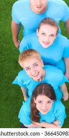 Group of young  people standing on green grass