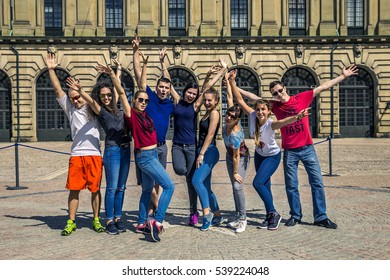 Group of young people standing and posing in front of camera with raised hands up, Stockholm, Sweden