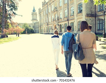 Group of young people students go to university together. Group of friends walking with backpacks. Education, study, adventure, travel, hike, people, friendship - concept.