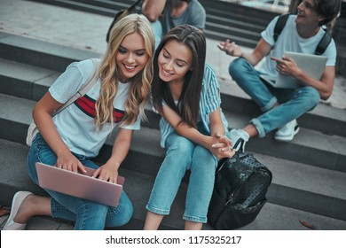 Group of young people are studying together in university. Students outdoors sitting on stairs.