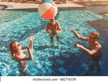 Group of young people in sunglasses are having fun in swimming pool, playing withinflatable ball and smiling.