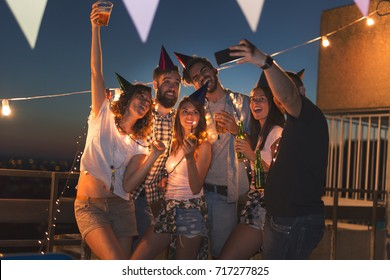 Group of young people taking selfie at a birthday party. Selective focus