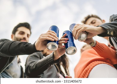 Group of young people toasting with canned beers. View from bottom, focus on the cans.