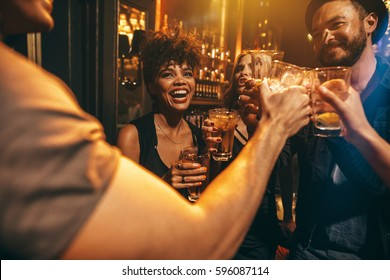 Group of young people toasting drinks at nightclub. Young men and women having fun at lounge bar.