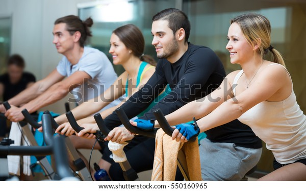 Group of young people training on exercise bikes in gym