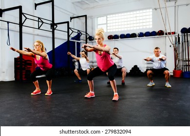Group of young people training squats at gym class.