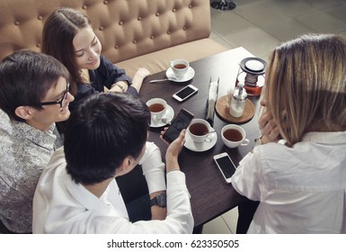 Group of young people from two couples of guys and girls have a tea time in the cafe and looking on the smartphone absorbedly