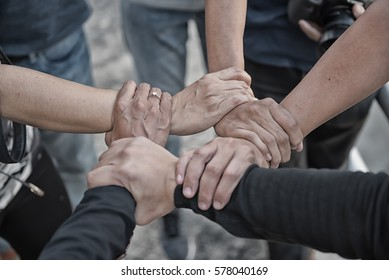 Group of young people United Hands together expressing positive , teamwork concepts.