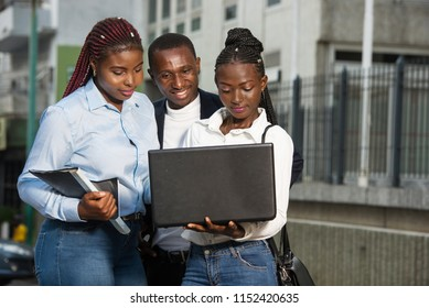 Group of young people using smart computers outdoors in urban context. Women and men sitting on the stairs in the street, wearing casual clothes.