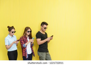 Group of young people using smartphone on wall. Network connection technology concept with free space.