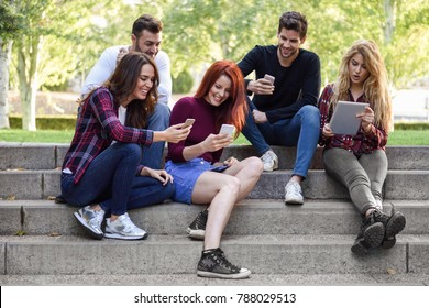 Group of young people using smartphone and tablet computers outdoors in urban background. Women and men sitting on stairs in the street wearing casual clothes.