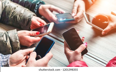 Group of young people using smartphones - Hands view of happy friends having fun with mobile phones apps - New technology trends, influencer and generation z concept - Main focus on bottom cellphones