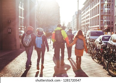 A group of young people walk the streets of Berlin in the winter. Some couples hold hands. Shot in backlight with a bright sun. December 2018.