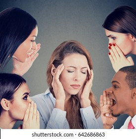 Group of young people whispering gossip to a stressed woman suffering from headache