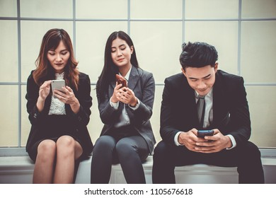 A group of young people who are wearing business attire are typing text message or surfing internet on their smartphones at the office
