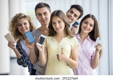 Group of young positive friends holding phones and posing to camera. Education concept.