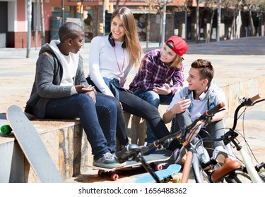 Group of young  positive  teenage friends relaxing and chatting in town square