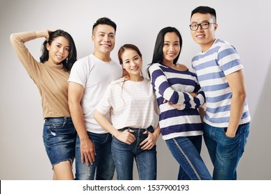 Group of young positive Vietnamese people in casual clothes posing together for studio portrait