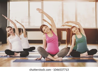Group of young pregnant women are doing relaxation exercise on exercise mat
