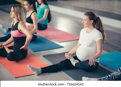 Group of young pregnant women doing relaxation exercise on exercising mat