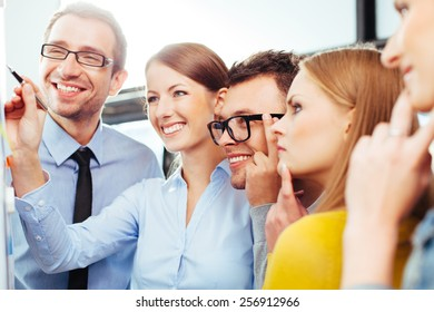 Group of young professional salespeople looking at a board with their results