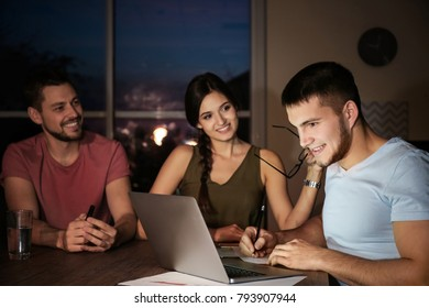 Group of young professionals having late night meeting in office