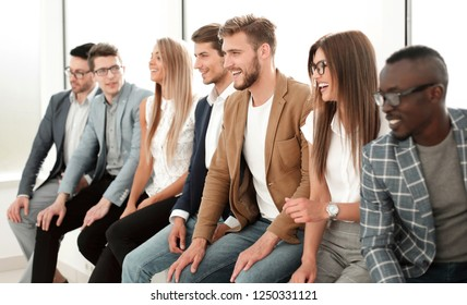 group of young professionals sitting near the wall