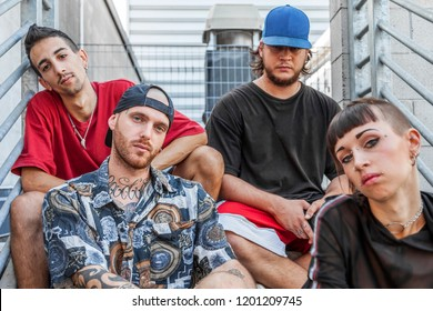 group of young rappers posing sitting on the metal stairs of an abandoned building