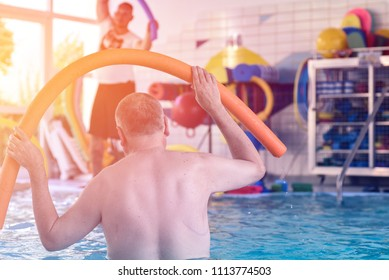 Group or young and senior people in aquarobic fitness swimming pool exercising
