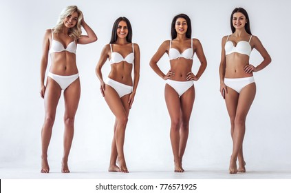 Group of young sexy multiracial women in white lingerie are posing on white background. Attractive women isolated.