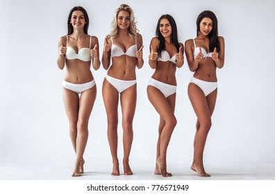 Group of young sexy multiracial women in white lingerie are posing on white background and showing thumbs up. Attractive women isolated.
