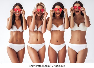 Group of young sexy multiracial women in white lingerie are posing on white background with red hearts in hands. Attractive women isolated. Saint Valentine's Day.