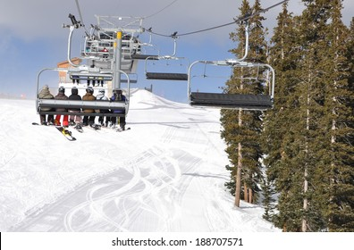 A group of young skiiers riding up the chair lift in Keystone, Colorado on winter vacation.